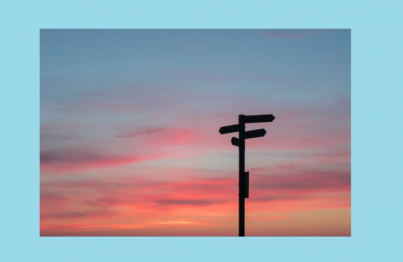 Image of pointed signs in the sunset sky